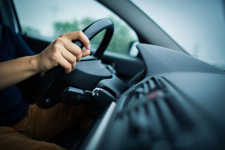 Male driver\'s hands driving a car on a highway  photo