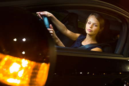 night stick: Driving a car at night - pretty, young woman driving her modern car at night, in a city (shallow DOF; color toned image)