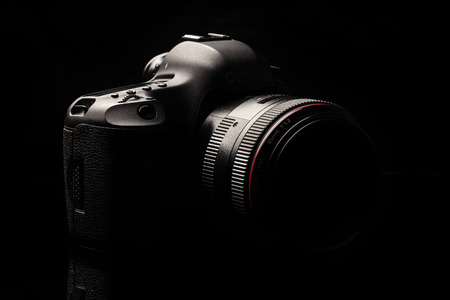 photojournalist: Professional modern DSLR camera low key image - Modern DSLR camera with a very wide aperture lens on