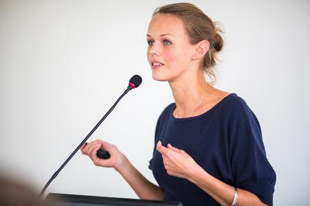 Hübsche, junge Geschäftsfrau, die eine Präsentation in einem Konferenz-  Tagungs Einstellung