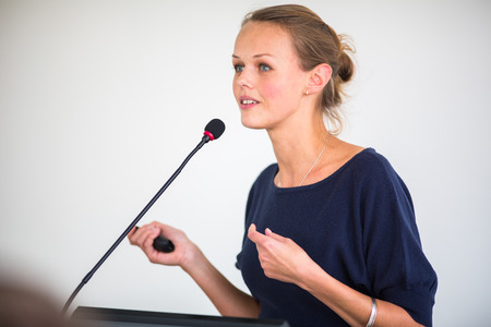 conference speaker: Pretty, young business woman giving a presentation in a conferencemeeting setting