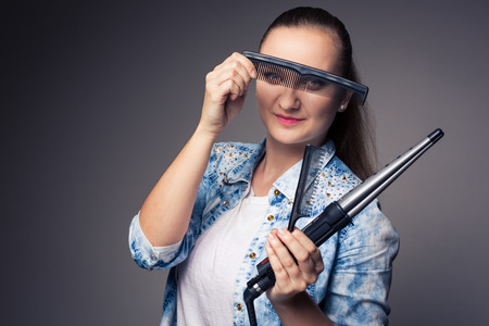 snipping: Funny portrait of a young female hairstylist, holding her tools and posing with a comb in front of her eyes ion front of a grey backdrop (color toned image; shallow DOF) Stock Photo
