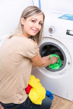 bright housekeeping: Housework: young woman doing laundry - putting colorful garments into the washing machine (shallow DOF; color toned image) Stock Photo