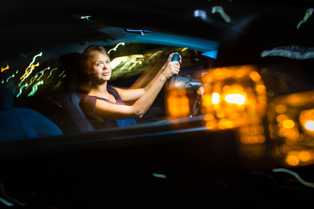 Driving a car at night - pretty, young woman driving her modern car at night, in a city (shallow DOF; color toned image) photo