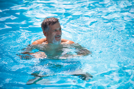1 mature man: Senior man in his home swimming pool, enjoying the deserved retirement