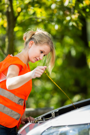 high visibility: Young female driver wearing a high visibility vest on the roadside after her car has broken down