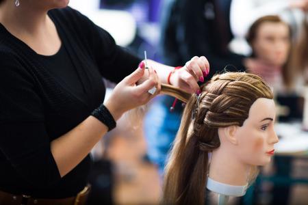 hairdresser scissors: Pretty female hairdresserhaidressing apprenticestudent training on an apprentice head Stock Photo