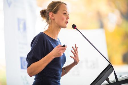 Bastante, joven mujer de negocios dando una presentación en un escenario de conferencias / reuniones (DOF, imagen en color entonado) Foto de archivo
