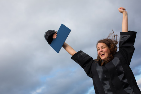 joyfully: Pretty, young woman celebrating joyfully her graduation - spreading wide her arms, holding her diploma, savouring her success (color toned image; shallow DOF) Stock Photo