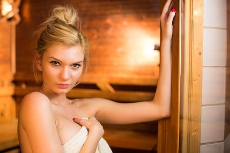 sauna nackt: Junge Frau, die Entspannung in der Sauna, die eine Pause von ihrem Terminkalender, kümmert sich um sich selbst und genießen die Wellness-Leistungen ihrer Arbeit bietet