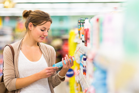 comprando: Hermosa mujer joven de compras en una tienda de alimentos  supermercado (imagen a color entonado) Foto de archivo