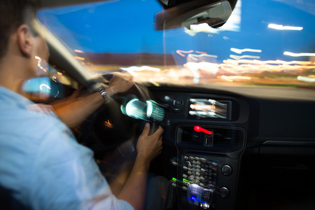 Driving a car at night - young man driving his modern car at night in a city (shallow DOF; color toned image, motion blur technique used to convey speed of the fast driving and drama) photo