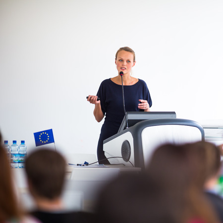 Pretty, young business woman giving a presentation in a conference/meeting setting (shallow DOF; color toned image). European Union flag on the table. Standard-Bild