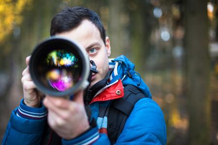 Junge männliche Fotografen, die Fotos mit seinem riesigen, neu, glänzend, schnell erstklassige professionelle Teleobjektiv