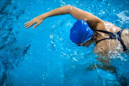 屋内スイミング プール - クロール (浅い被写し界深度) をやっているの女子水泳選手