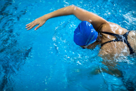 Female swimmer in an indoor swimming pool - doing crawl (shallow DOF) Stockfoto