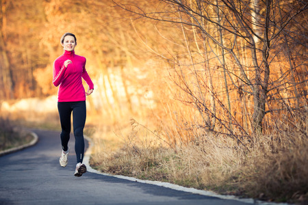people jogging: Mujer joven correr al aire libre en un parque de la ciudad en una fr�a de oto�o  invierno d�a