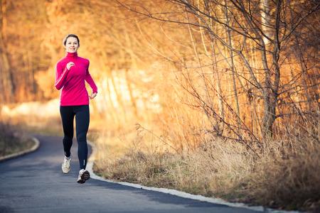 frio: Mujer joven correr al aire libre en un parque de la ciudad en una fría de otoño  invierno día