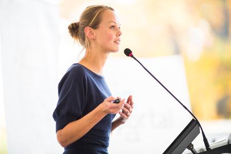 hablar en publico: Bastante, joven mujer de negocios dando una presentación en un escenario de conferencias  reuniones (DOF, imagen en color entonado)