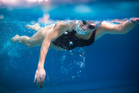 crawl: Female swimmer in an indoor swimming pool - doing crawl (shallow DOF) Stock Photo