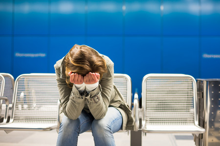 Sad and alone in a big city - Depressed young woman sitting in a metro station, feeling sorrow, regret Stock Photo