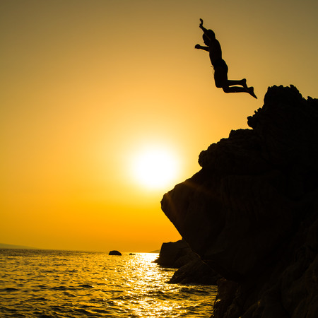 leap: Boy jumping to the sea. Silhouette shot against the sunset sky. Boy jumping off a cliff into the ocean. Summer fun lifestyle.