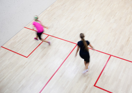 Two female squash players in fast action on a squash court (motion blurred image; color toned image) photo