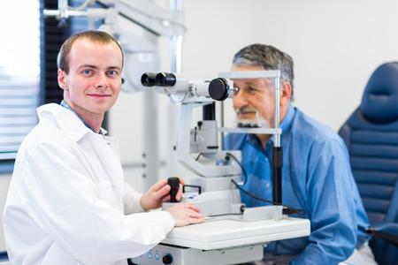 Optometrie concept - mooie jonge vrouw met haar ogen onderzocht door een oogarts