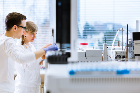 Two young researchers carrying out experiments in a lab (shallow DOF; color toned image) photo