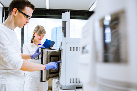 researchers: Two young researchers carrying out experiments in a lab (shallow DOF; color toned image) Stock Photo