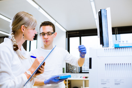 scholarship: Two young researchers carrying out experiments in a lab (shallow DOF; color toned image) Stock Photo
