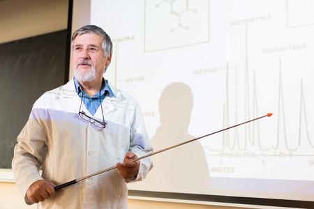 profesor: Profesor de qu�mica mayor que da una conferencia en frente de aula lleno de estudiantes (DOF, imagen en color entonado)