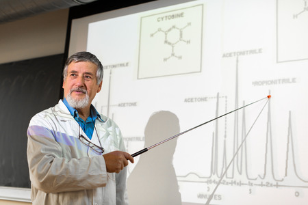Profesor de química mayor que da una conferencia en frente de aula lleno de estudiantes (DOF, imagen en color entonado) Foto de archivo