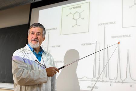 Senior professor chemie geeft een lezing in de voorkant van klas vol leerlingen (ondiepe DOF, kleur getinte afbeelding)