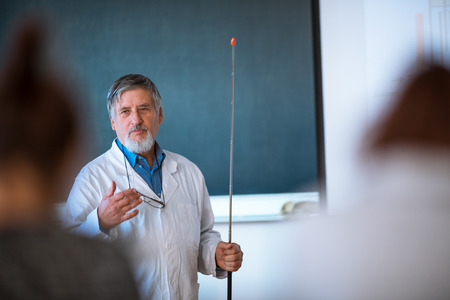 professor: Senior chemistry professor giving a lecture in front of classroom full of students (shallow DOF; color toned image) Stock Photo