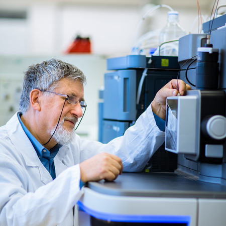 dof: Senior male researcher carrying out scientific research in a lab (shallow DOF; color toned image)