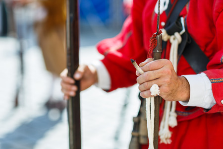 musketeer: Hands of a musketeer holding a musekt and slow match or match cord with a glowing tip, ready to ignite the gunpowder and fire Stock Photo