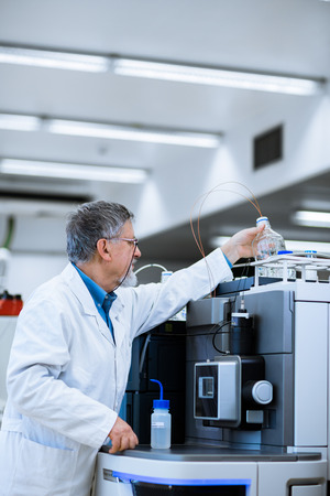 lab coats: Senior male researcher carrying out scientific research in a lab (shallow DOF; color toned image)