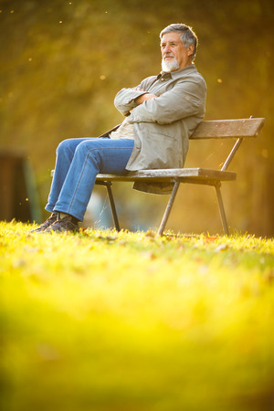 Senior man sitting on a bench in a park, enjoying retirement
