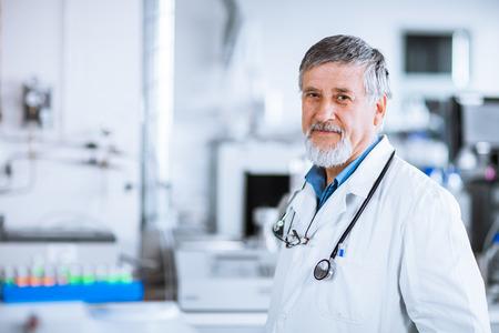 Senior arts met behulp van zijn tablet-computer op het werk (kleur getinte afbeelding)