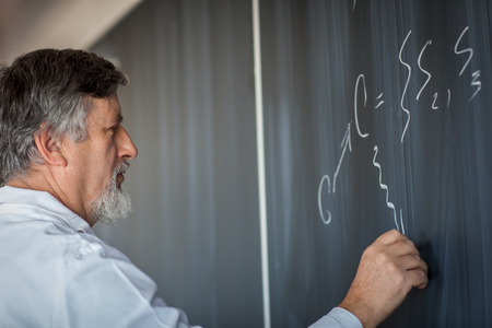 secondary: Senior chemistry professor writing on the board while having a chalk and blackboard lecture (shallow DOF; color toned image)