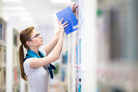 choose university: Pretty, female college student in a library, looking for a book (shallow DOF; color toned image) Stock Photo