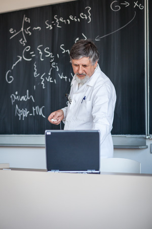 college professor: Senior chemistry professor writing on the board while having a chalk and blackboard lecture (shallow DOF; color toned image)