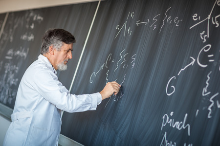 Senior chemistry professor writing on the board while having a chalk and blackboard lecture (shallow DOF; color toned image)