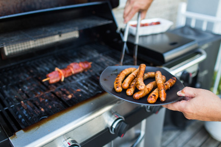 BBQ with sausages and red meat on the grill - male hands holding a plate and taking the meat off the grill before it is too late