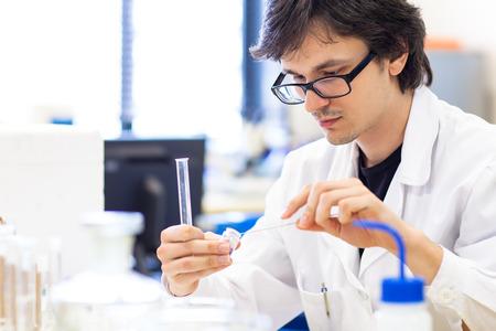 investigando: Hombre investigador llevar a cabo la investigaci�n cient�fica en un laboratorio (DOF, imagen en color entonado) Foto de archivo