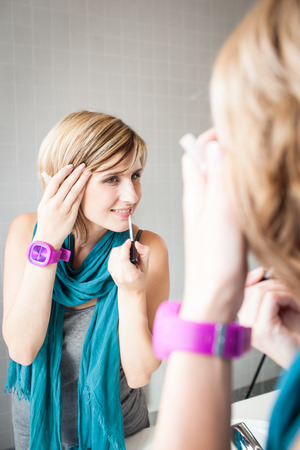 Pretty, young woman applying mascara /eyeshadows in front of a mirror photo