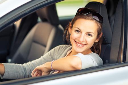 Jolie jeune femme au volant de sa nouvelle voiture (image couleur tonique; shallow DOF)