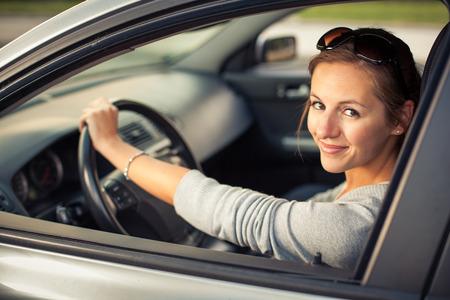 cinturon seguridad: Mujer bonita joven que conduce su nuevo coche (imagen a color entonado, DOF bajo) Foto de archivo