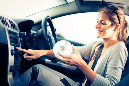 asiento coche: Conductor joven mujer tocando m�sica en el coche (cambiar de CD) Foto de archivo
